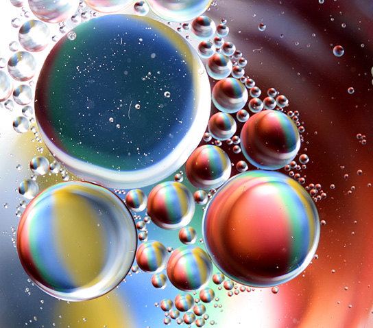 Image shows oil droplets floating in water. The oil droplets act like prisms that bend the light into all the colors of the rainbow.