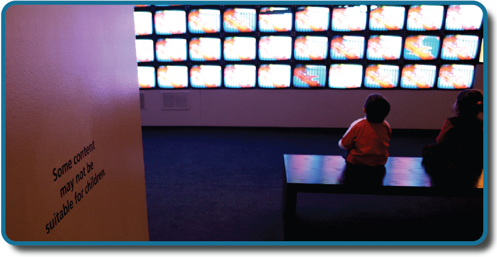 "Children sit in front of a bank of television screens. A sign on the wall says, ""Some content may not be suitable for children."""