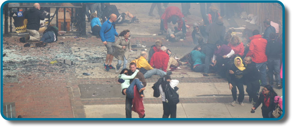 A photograph shows a crowd  at the site of the Boston Marathon bombing immediately after it occurred. Debris is scattered on the ground, several people appear to be injured, and several people are helping others.