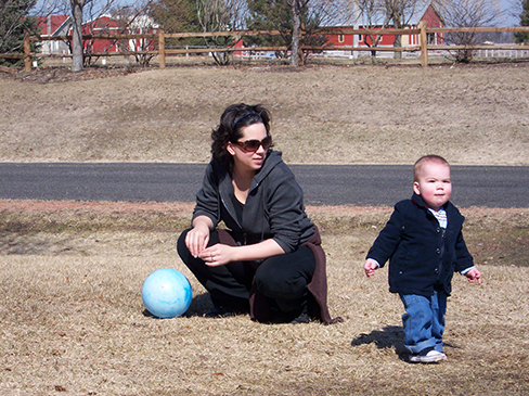A photograph shows a person squatting down next to a small child who is standing up.