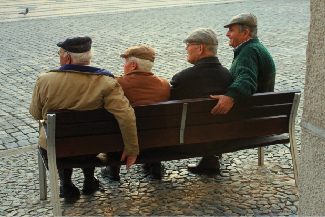 Four people are sitting on a bench looking off in the same direction.
