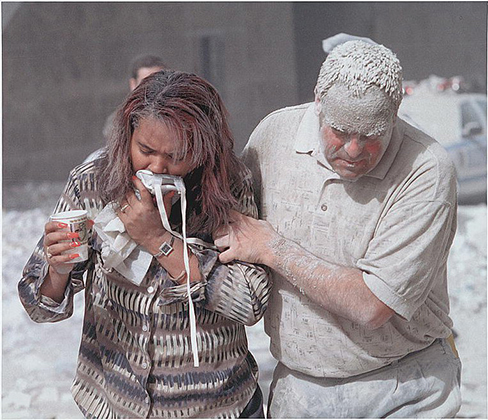 A photograph shows two people covered in dust; one appears to be helping the other.