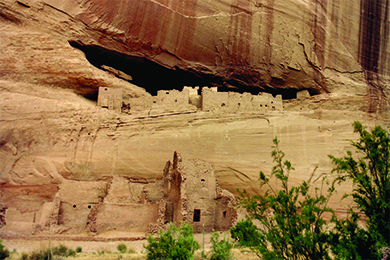 A photograph of Anasazi cliff dwellings shows blocky adobe structures with window and door openings, some of which are set atop a high, sheer cliff.