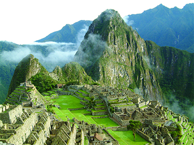 A photograph of Machu Picchu shows the ruins of a complex of buildings with stone walls, stepped terraces green with grass, and a pyramid, with high mountains in the background.