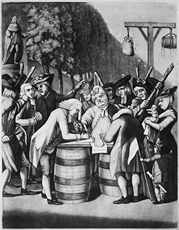 An engraving shows a merchant signing a non-importation agreement outdoors on a makeshift table of barrels, surrounded by a crowd of stern-looking people holding thick sticks. Behind him, another man, forcibly held by a group of threatening-looking men, is apparently next in line to sign the agreement. In the background, a bag of tar and a bag of feathers hang from a wooden structure.
