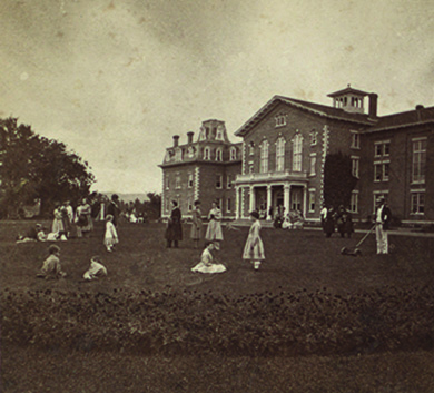 A photograph depicts a large, opulent house surrounded by a lawn on which men, women, and children sit, stand, and converse.