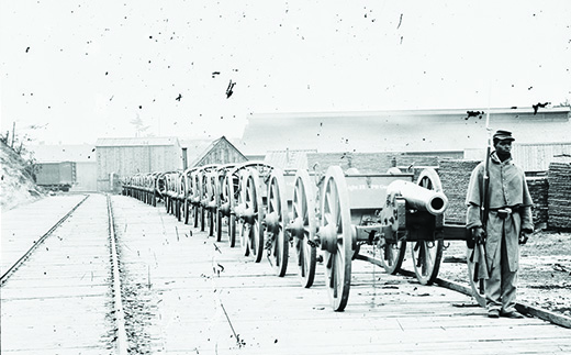 A photograph shows an African American soldier standing in front of a long line of cannons alongside a railroad track.