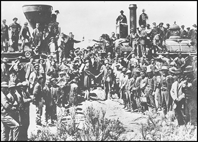 A photograph shows the ceremony commemorating the completion of the first transcontinental railroad. Samuel S. Montague and Grenville M. Dodge, chief engineers of the Central Pacific and Union Pacific Railroads, respectively, shake hands symbolically in front of two locomotives and a crowd of workers.