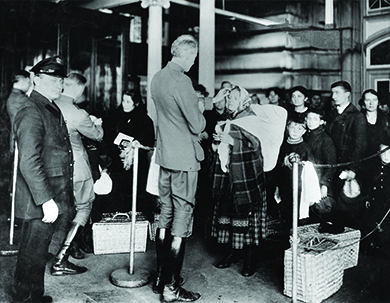 A photograph shows inspectors examining newly arrived immigrants at Ellis Island.