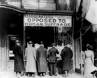 """A photograph shows five men and a woman standing outside of a building labeled """"Headquarters National Association Opposed To Woman Suffrage."""""""