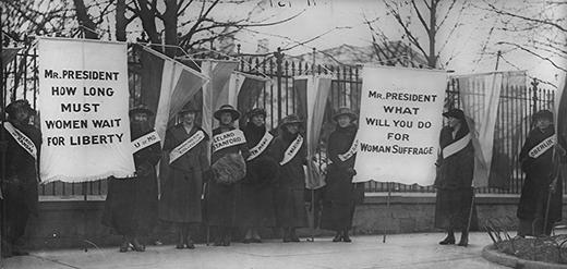 """A photograph shows Alice Paul and the Silent Sentinels picketing outside of the White House. Each woman wears a banner stating her alma mater. The women hold two large signs, the first of which reads """"Mr. President/How Long Must Women Wait For Liberty."""" The second sign reads """"Mr. President/What Will You Do For Woman Suffrage."""""""