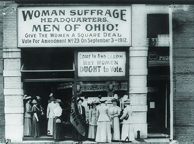 """A photograph shows women suffragists standing outside a building. The sign above them reads """"Woman Suffrage Headquarters. Men of Ohio! Give The Women A Square Deal. Vote For Amendment No. 23 on September 3—1912."""" A second sign reads """"Come In And Learn Why Women OUGHT to Vote."""""""