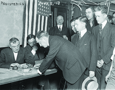 A photograph shows a group of young men registering for military conscription.