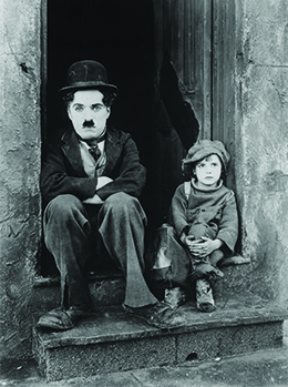 Charlie Chaplin is shown sitting in a doorway with his arms folded, accompanied by a small, shabbily dressed child.