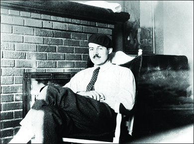 A photograph shows Ernest Hemingway reclining in a chair in front of a fireplace.
