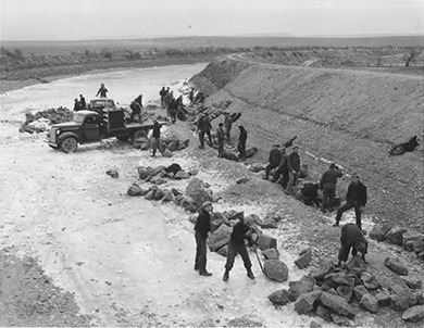 A photograph shows a group of CCC workers building a canal.