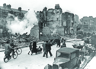 A photograph shows a destroyed London street in which most of the buildings have been reduced to rubble; citizens stroll past with bicycles and a child in a pram