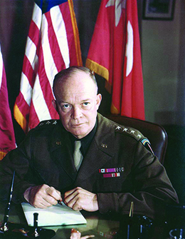 A photograph shows Dwight Eisenhower seated at a desk in his military uniform.