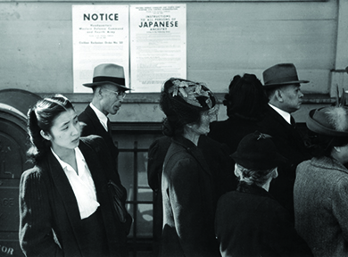 A photograph shows Japanese Americans standing in line in front of a poster detailing internment orders in California.
