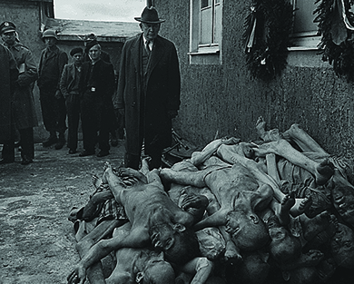 A U.S. senator, congressional committee member, and several other officials examine a massive heap of emaciated corpses at the Buchenwald concentration camp.