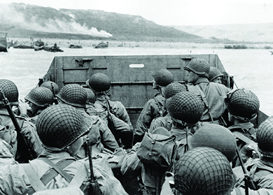 A photograph shows U.S. troops in a military landing craft approaching a beach. Ships are visible in the far distance.
