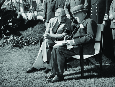 A photograph shows Winston Churchill and President Roosevelt seated outdoors in chairs, convening over papers, with a row of officials standing behind them.