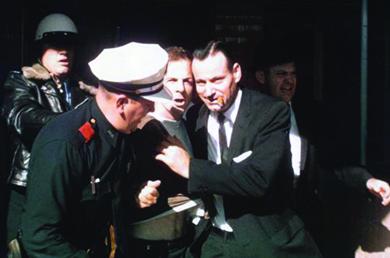 A photograph shows several men arresting Lee Harvey Oswald.