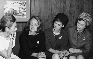 A photograph shows Betty Friedan and three other women engaged in conversation.