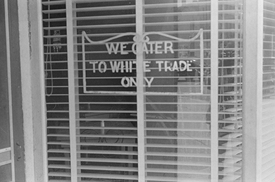 """A photograph shows a shop window bearing a sign that reads """"We cater to white trade only."""""""