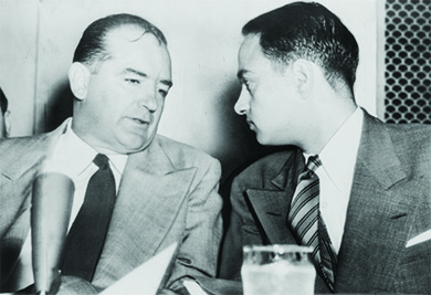 A photograph shows Joseph McCarthy and Roy Cohn engaged in a quiet conversation.