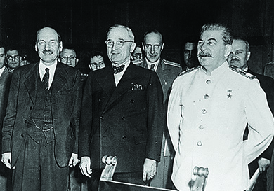 A photograph shows Clement Atlee, Harry Truman, and Joseph Stalin standing in front of a group of officials.