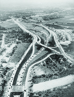 An aerial photograph shows a network of newly constructed highways.