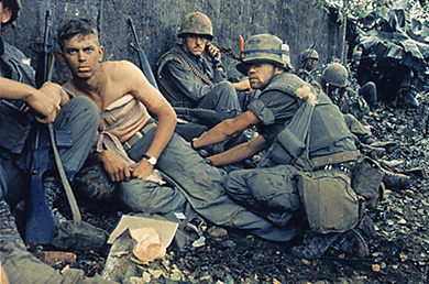 A photograph shows a group of uniformed U.S. soldiers crouched beside a wall. One soldier is shirtless, with a large bandage wrapped around his chest.