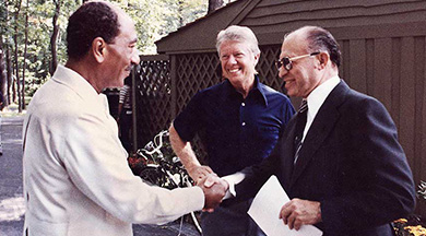 A photograph shows Jimmy Carter standing by as Anwar Sadat shakes hands with Menachem Begin.