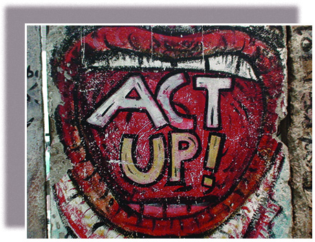 "A panel of graffiti on the Berlin Wall shows a wide-open mouth, within which are the words ""ACT UP!"""