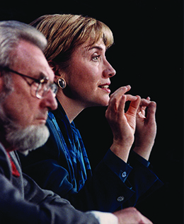 A photograph shows C. Everett Koop and Hillary Clinton in profile. They sit beside one another; Clinton speaks and gestures with her hands.
