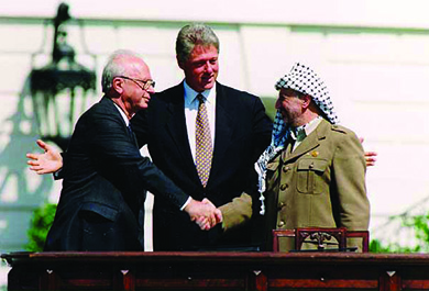 A photograph shows Yitzhak Rabin and Yasser Arafat shaking hands. Bill Clinton stands between them with his arms open in a welcoming gesture.