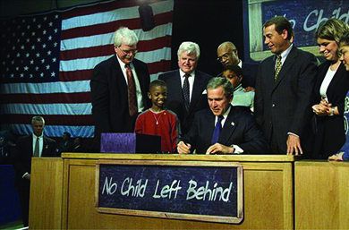 "A photograph shows President Bush signing the No Child Left Behind Act at a large desk, surrounded by U.S. officials and several children. On the desk hangs a chalkboard that reads ""No Child Left Behind."""