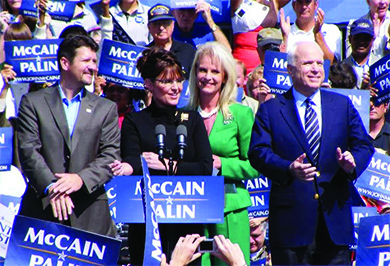 "A photograph shows John and Cindy McCain and Sarah and Todd Palin standing at a lectern, surrounded by supporters holding ""McCain / Palin"" signs."