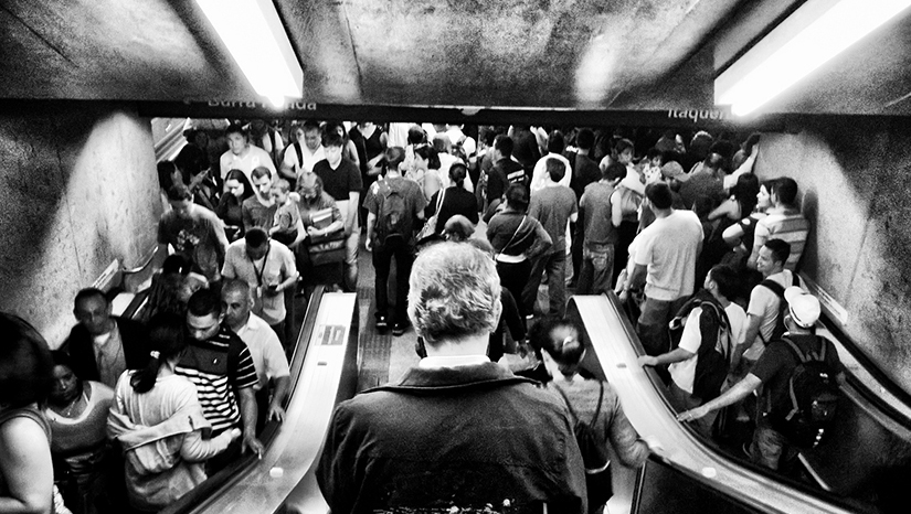 A photo of a crowded subway station full of people going up and down escalators