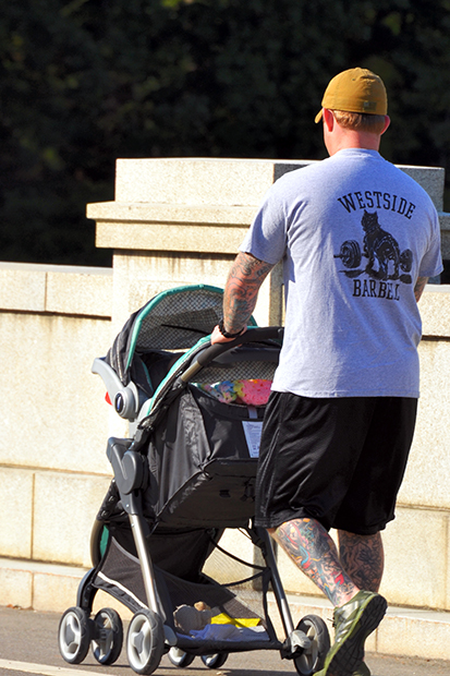 A photo of a man with many tattoos on his legs, pushing a baby stroller outside