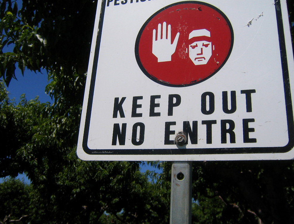 A keep out sign with text in English and Spanish is shown.