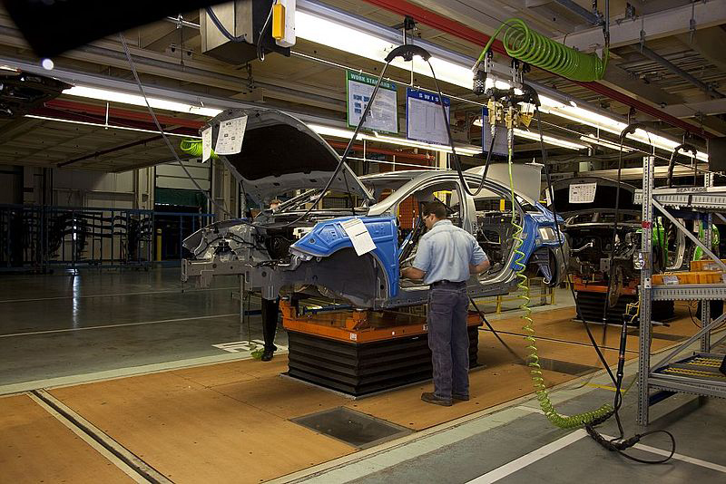 A man is shown using a machine to install car parts on an assembly line.