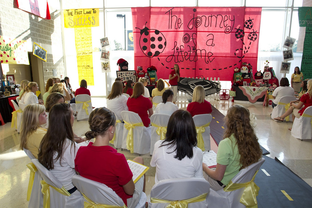 About a dozen young females are shown sitting in chairs at a sorority recruitment on campus.