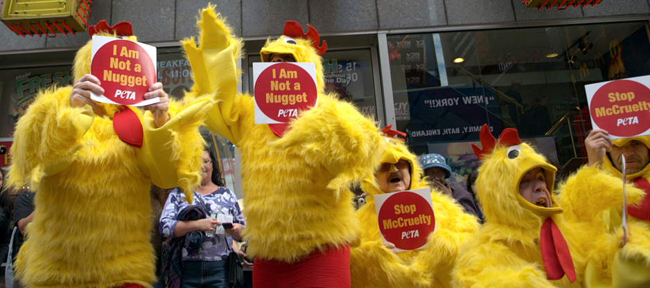 """Protesters are shown here wearing yellow chicken costumers and holding PETA signs that say """"I Am Not a Nugget"""" and """"Stop McCruelty."""""""