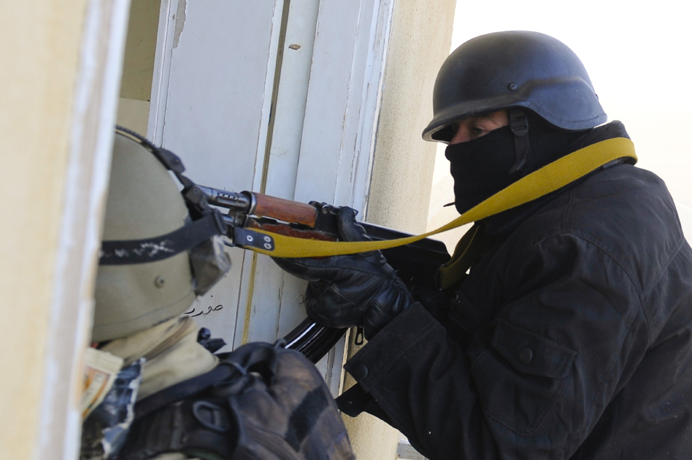 An armed and armored police officer is shown in a doorway with his gun.