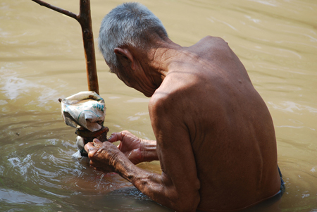 A shirtless elderly man is shown manipulating a large tree branch while standing waist-deep in a river.
