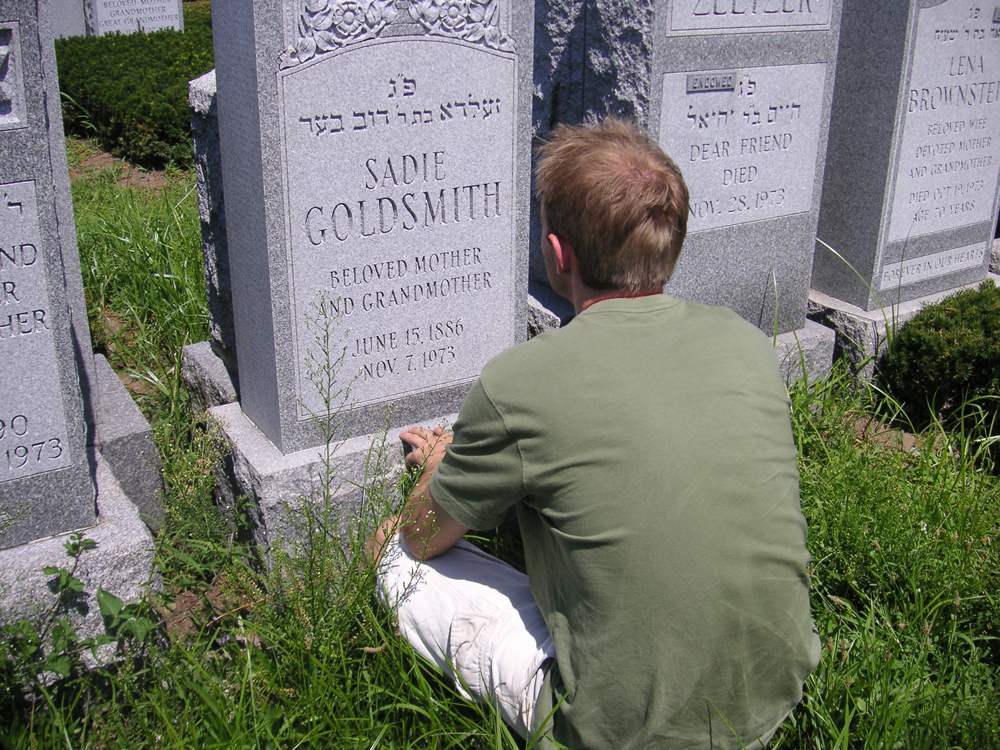A young man in a green T-shirt and white shorts is shown sitting in the grass in front of a gravestone.