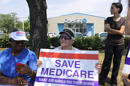 """Two elderly women, one holding a red white and blue sign reading """"Save Medicare: Make Big Banks Pay Their Share,"""" are shown sitting under some trees and in front of a suburban bank building. A younger woman, dressed all in black, is shown behind and to the left of the other women."""