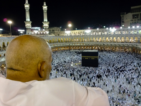 A man dressed in white is shown from behind looking down over the Kaaba, Islam's most sacred site. Hundreds of other people, dressed in all black or all white, can be seen circling a large black cube-like structure on the floor of a stadium-like structure.